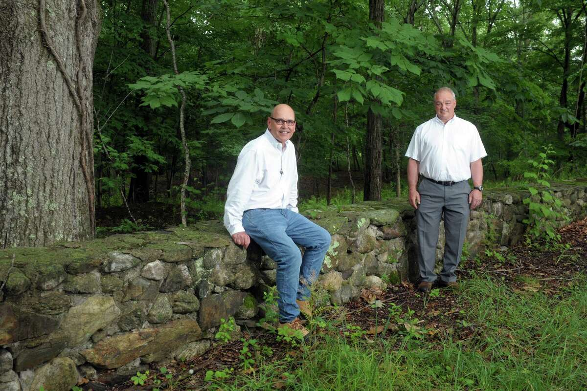 Aspetuck Land Trust President Bill Kraekel, left, and Easton First Selectman David Bindelglass pose during a tour of a property the land trust will receive following a recent grant, in Easton, Conn. July 1, 2021. The property will add to the land trust's Warner Angler Preserve along the Mill River.