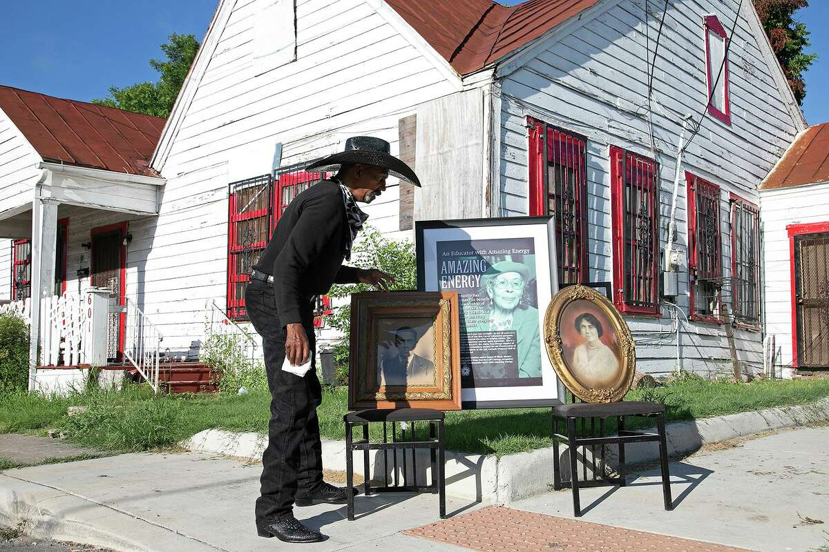 Ernest Stevenson Qadimasil II adjusts photographs of his mother, Henrietta Eugene Roberts Stevenson, center, who was born in the house behind him in 1915, and his grandparents, Lawyer Henry Porterfield Roberts, left, and Ira Aldridge Kilpatrick Roberts, outside the home where his grandparents lived with his mother in San Antonio on July 2, 2021.
