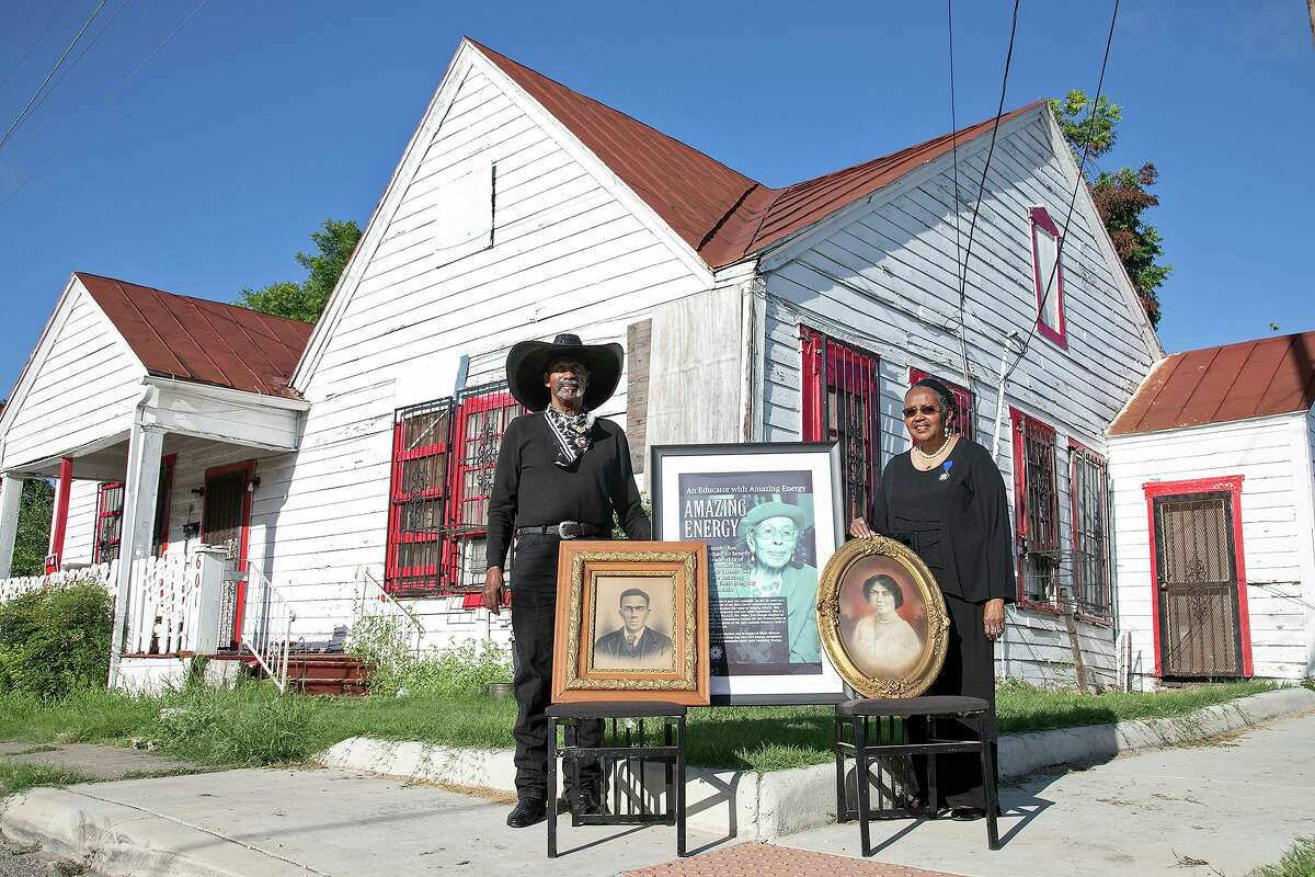 Ernest Stevenson Qadimasil II and his sister, Maria Stevenson Greene, stand with photographs of their mother, Henrietta Eugene Roberts Stevenson, center, who was born in the house behind them in 1915, and their grandparents, Lawyer Henry Porterfield Roberts, left, and Ira Aldridge Kilpatrick Roberts, outside the home where their grandparents lived with their mother in San Antonio on July 2, 2021.