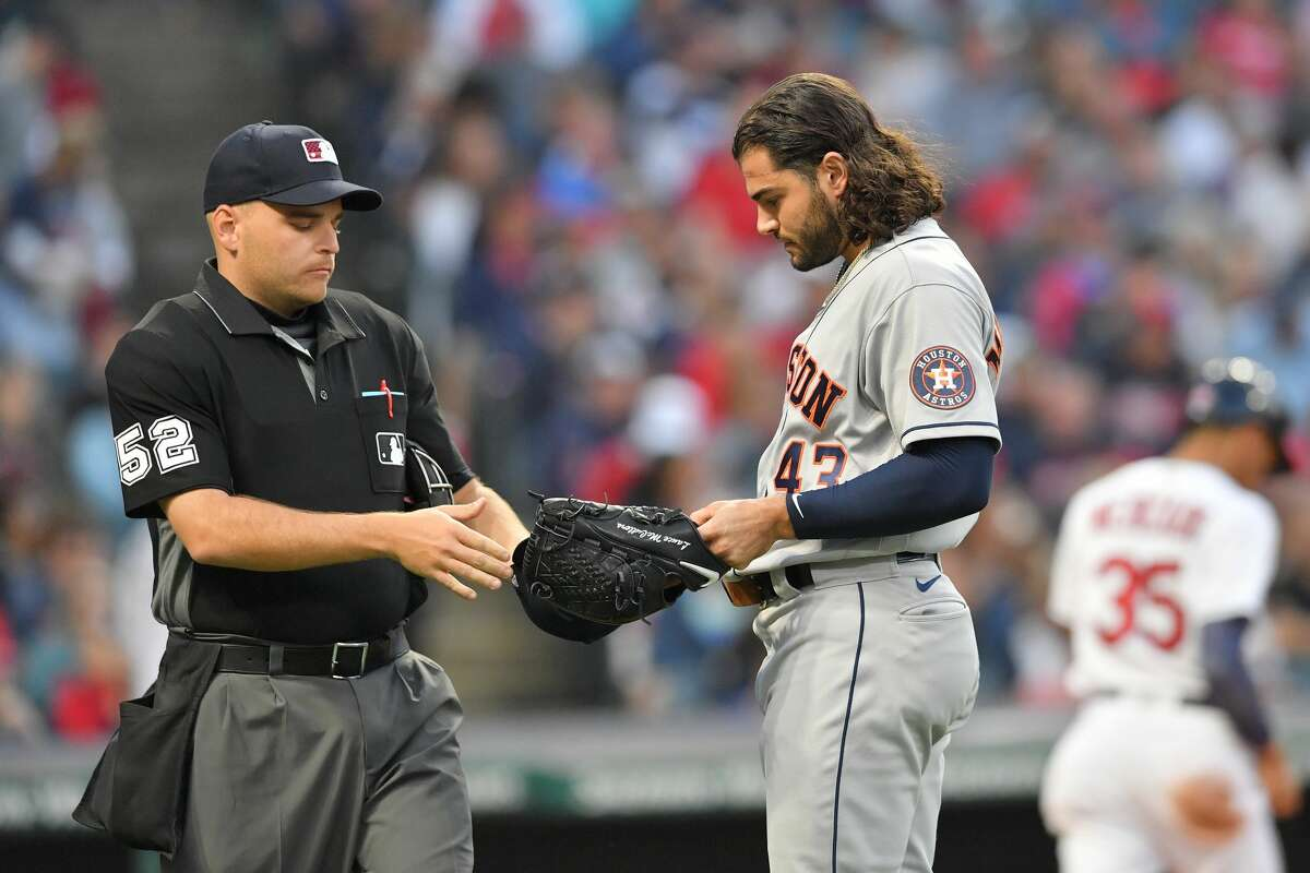 CLEVELAND, OHIO - JULY 02: Home plate umpire Jansen Visconti #52 checks the hat of starting pitcher Lance McCullers Jr. #43 of the Houston Astros for foreign substances after the fourth inning against the Cleveland Indians at Progressive Field on July 02, 2021 in Cleveland, Ohio. (Photo by Jason Miller/Getty Images)