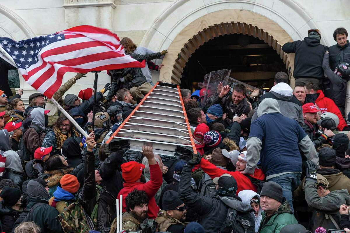 Insurrectionists refusing to accept President Donald Trump's defeat clash with police outside the U.S. Capitol on Jan. 6.