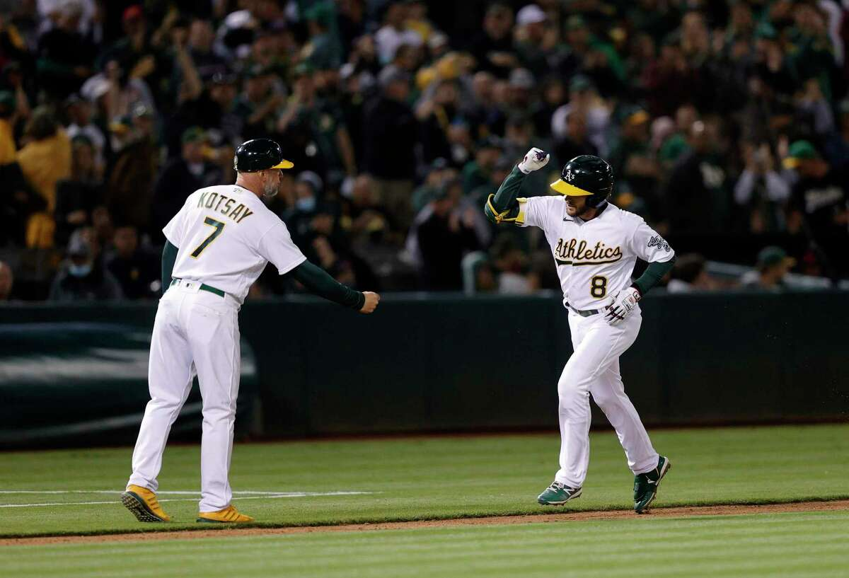 OAKLAND, CALIFORNIA - JULY 02: Jed Lowrie #8 of the Oakland Athletics is congratulated by Mark Kotsay #7 after he hit a home run in the seventh inning against the Boston Red Sox at RingCentral Coliseum on July 02, 2021 in Oakland, California. (Photo by Ezra Shaw/Getty Images)