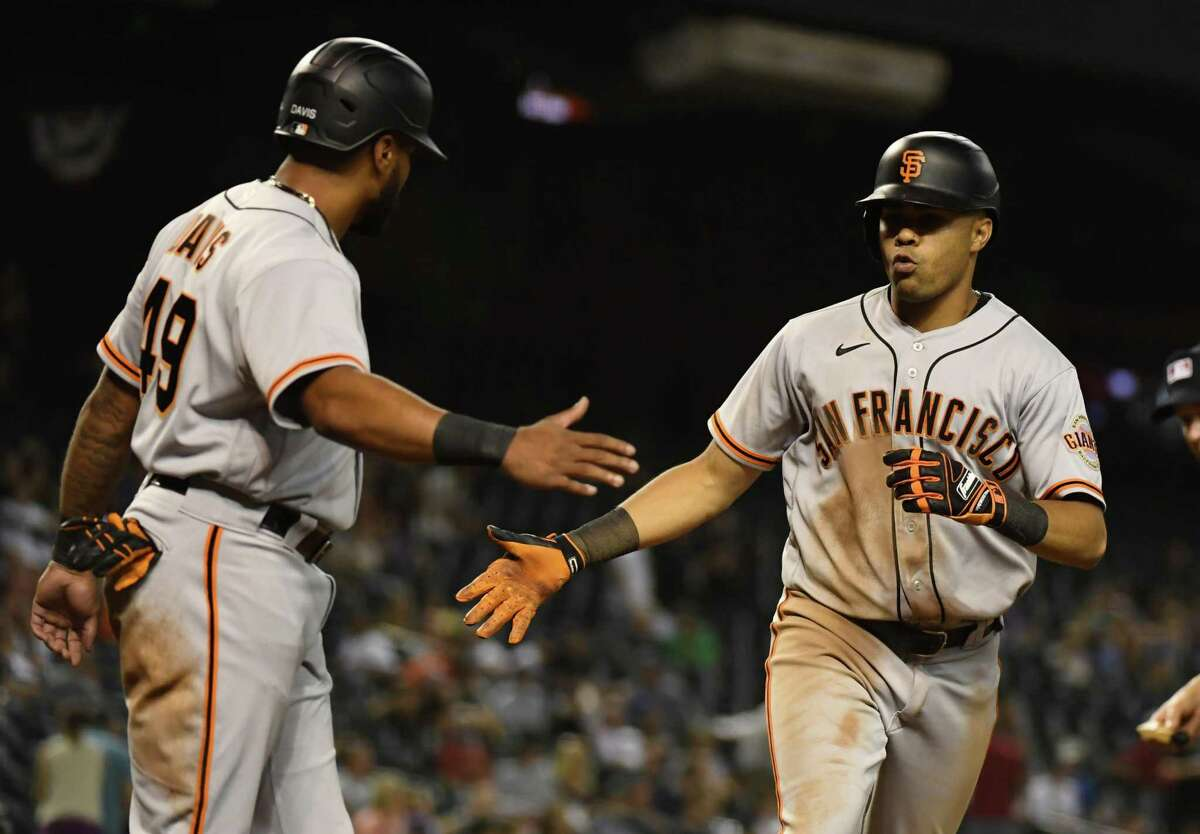 PHOENIX, ARIZONA - JULY 02: LaMonte Wade #31 of the San Francisco Giants celebrates with Jaylin Davis #49 after hitting a two-run home run off of Brett De Geus #59 of the Arizona Diamondbacks during the eighth inning at Chase Field on July 02, 2021 in Phoenix, Arizona. (Photo by Norm Hall/Getty Images)