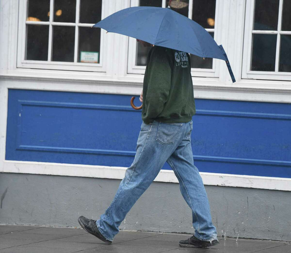A man walks along Main Steet with an umbrella as rain pours down in Stamford in April 2020. Rain is expected at the start of the July 4th weekend.