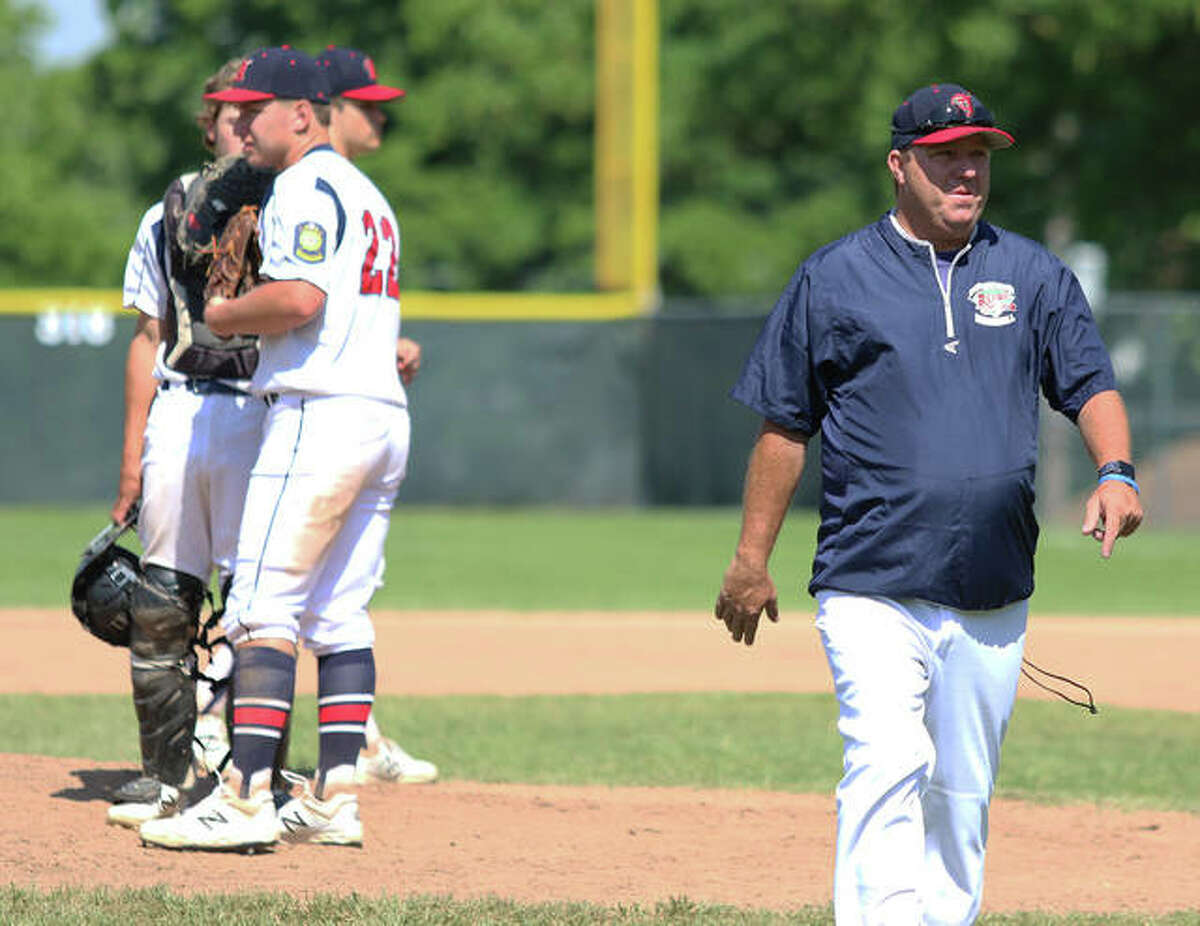 Alton Legion coach Doug Booten (right) walks back to the dugout after a mound visit during a game last summer. Post 126 is competing this weekend in the annual Firecracker Classic at Fairview Heights.