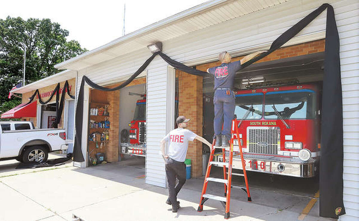 Firefighters erect black bunting on the front of the South Roxana Fire Station Friday after their chief, Todd Werner, 48, passed away unexpectedly Thursday. Details of the funeral arrangements for Chief Werner were announced early Saturday.