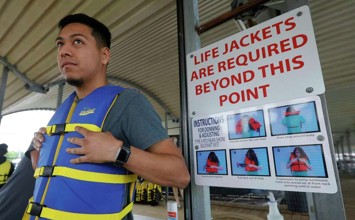 Cesar Escalante wearsa a life vest before going out on a boat with friends and family, Friday, May 14, 2021, in Conroe. The business has invested more than $50,000 in changes, such as a new life jacket cage.