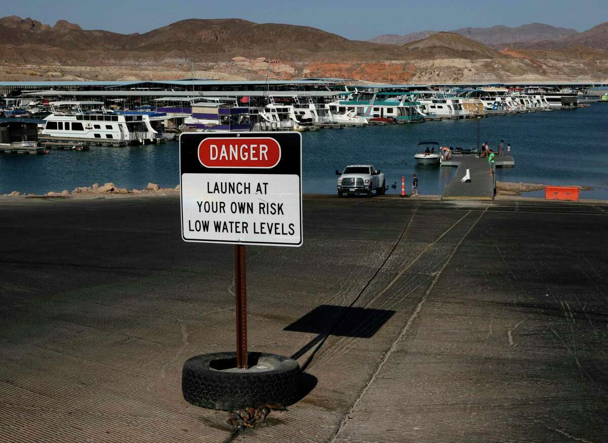 LAKE MEAD NATIONAL RECREATION AREA, NEVADA - JUNE 21: A sign at Callville Bay warns boaters of low water levels as visitors prepare to launch a boat on June 21, 2021 in the Lake Mead National Recreation Area, Nevada. The U.S. Bureau of Reclamation reported that Lake Mead, North America's largest artificial reservoir, dropped to just over 1,070 feet above sea level over the weekend, the lowest it's been since being filled in 1937 after the construction of the Hoover Dam. As a result of low lake levels, the National Park Service has had to close some boat launch ramps and use pipe mats to extend others temporarily.