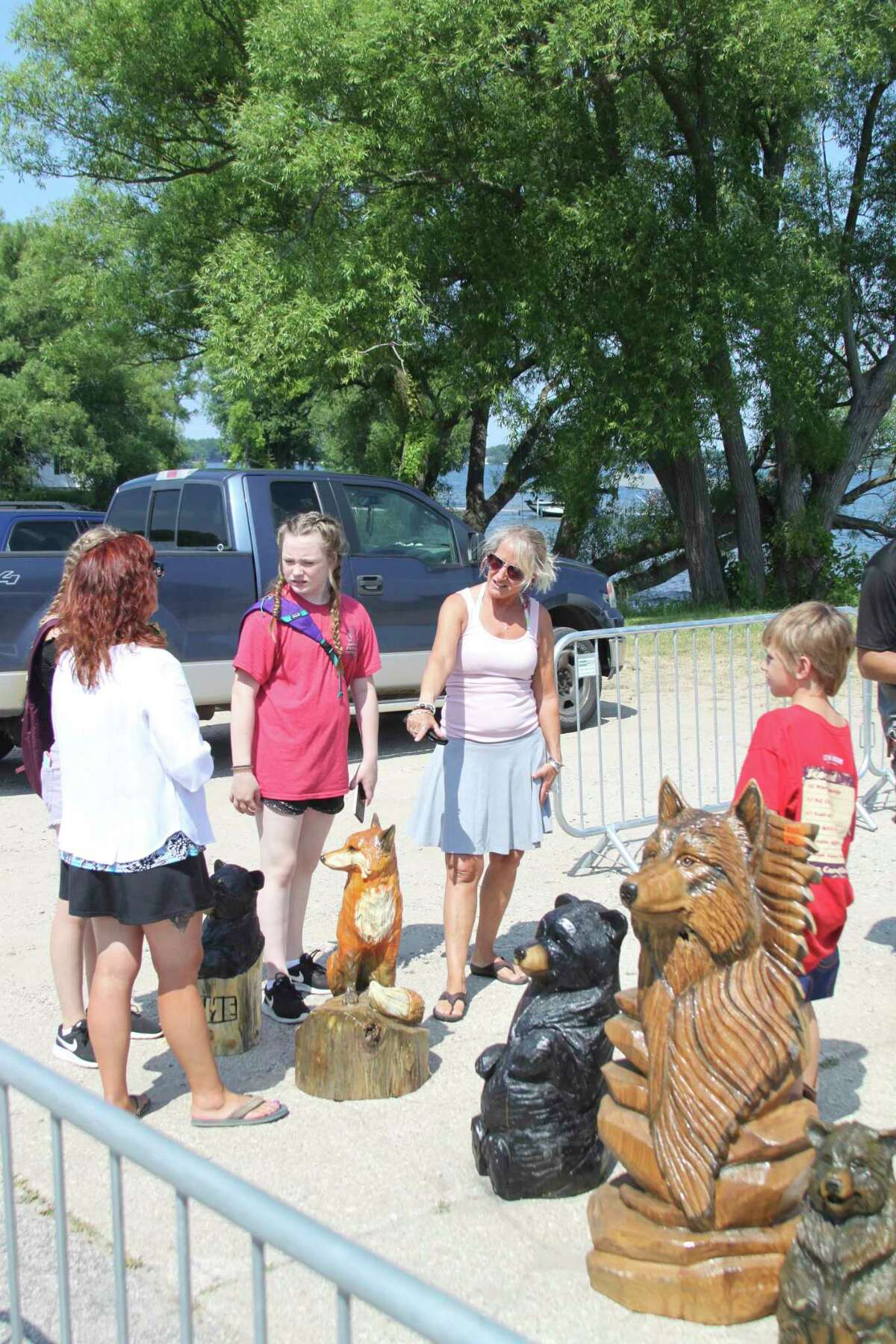 People look over some of the work of the Adams Chainsaw Art & Sawmill that came to Bear Lake Days all the way from Missouri for a previous event. This year, the chainsaw art will return to Bear Lake Days from 9 a.m. to 8 p.m. on Saturday near the Hopkins Park entrance. (File photo)