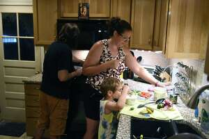 Times Union music critic Jim Shahen, left, and wife, Brielyn Smith, are assisted by their son, Issac, 5, as they prepare a family dinner on Wednesday, June 30, 2021, at their home in Bethlehem, N.Y.   (Will Waldron/Times Union)