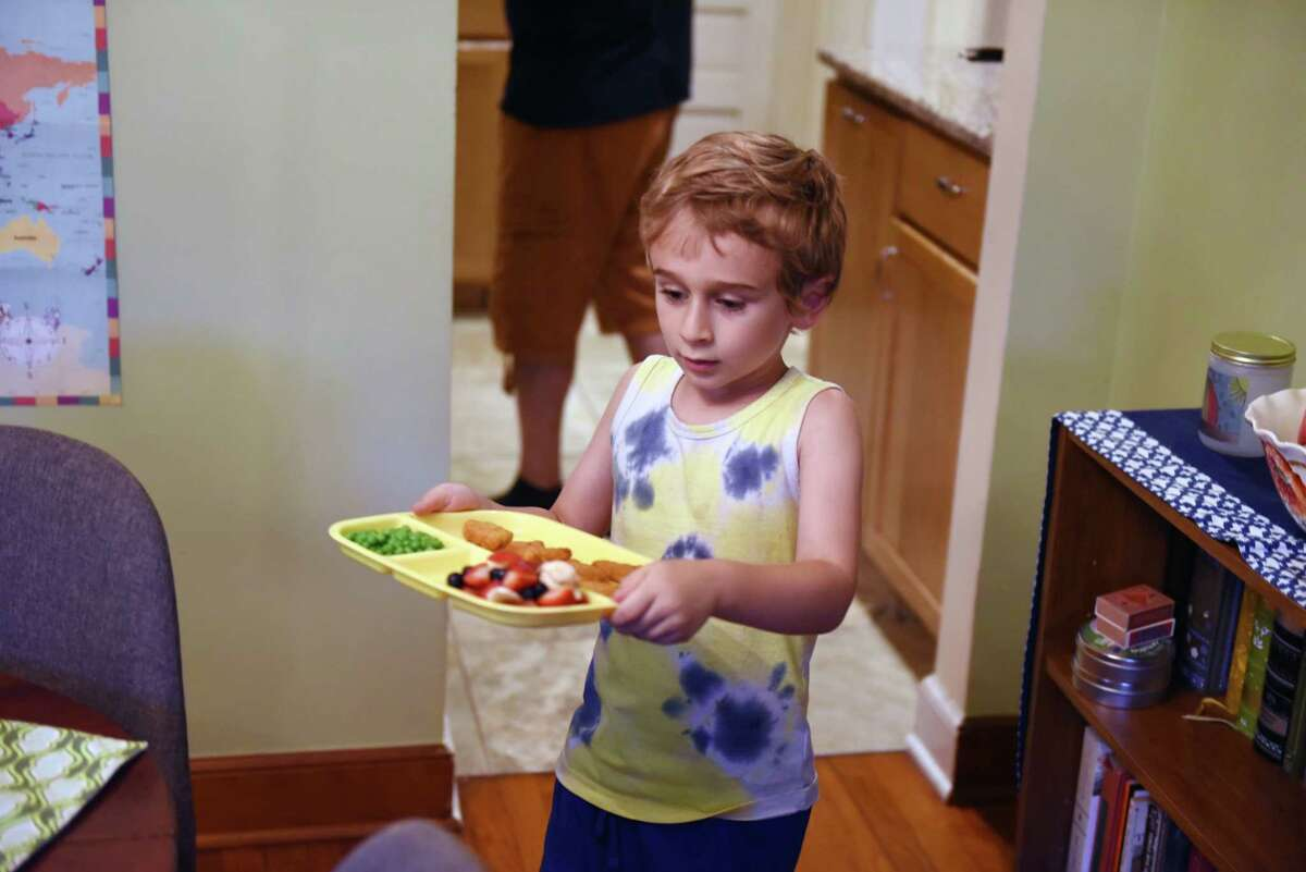 Isaac, 5, carries his dinner to the table as parents Jim Shahen and Brie Smith prepare their family meal. (Will Waldron/Times Union)