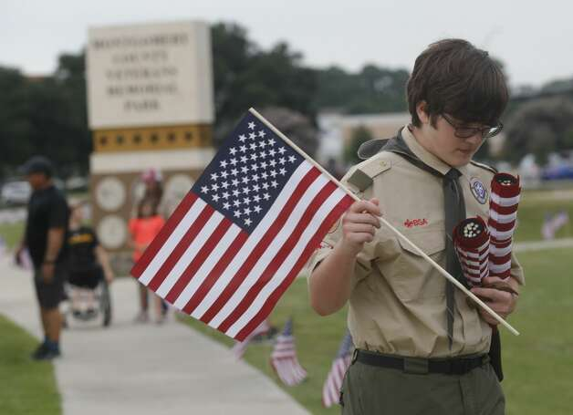 Zane Maples with Troop 1517 helps troop members and other Boy Scouts place American flags Friday along the paths at the Montgomery County Veterans Memorial Park to mark the July Fourth holiday, Friday, July 2, 2021, in Conroe. Photo: Jason Fochtman/Staff Photographer / 2021 © Houston Chronicle