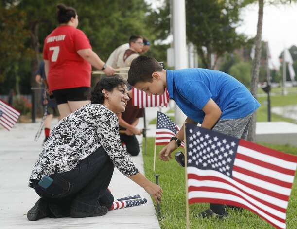 Charlene Bader helps her son, Joshua, place American flags along the paths at the Montgomery County Veterans Memorial Park to mark the July Fourth holiday, Friday, July 2, 2021, in Conroe. Photo: Jason Fochtman/Staff Photographer / 2021 © Houston Chronicle