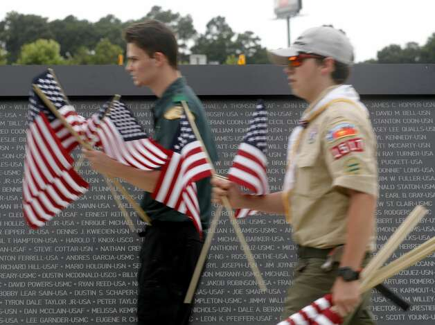 Boy Scouts Zack Avila and Mike Mcauliffe help place American flags Friday along the paths at the Montgomery County Veterans Memorial Park to mark the July Fourth holiday, Friday, July 2, 2021, in Conroe. Photo: Jason Fochtman/Staff Photographer / 2021 © Houston Chronicle