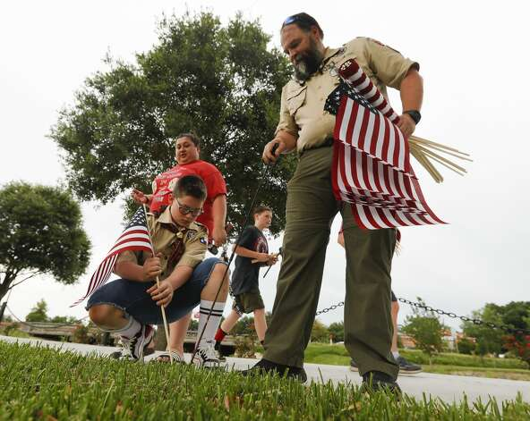Kevin Booth, assistant scoutmaster with Troop 1517, helps Caden Chupurdy place American flags along the paths at the Montgomery County Veterans Memorial Park to mark the July Fourth holiday, Friday, July 2, 2021, in Conroe. Photo: Jason Fochtman/Staff Photographer / 2021 © Houston Chronicle