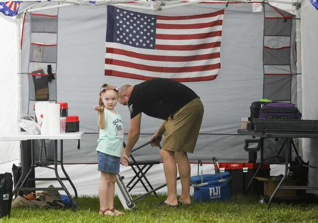 Aubree Booth catches rain in her hand as her dad, Nathan, packs up his vendor tent after heavy rain slowed visitors during Montgomery Freedom Fest, Saturday, July 3, 2021, in Montgomery. Photo: Jason Fochtman/Staff Photographer / 2021 ? Houston Chronicle