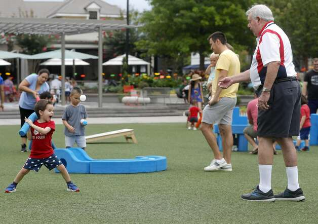 Howard Van Pelt, right, tosses a ball to his grandson, Aiden Langley, during a Fourth of July parade at Market Street, Saturday, July 3, 2021, in The Woodlands. Photo: Jason Fochtman/Staff Photographer / 2021 ? Houston Chronicle