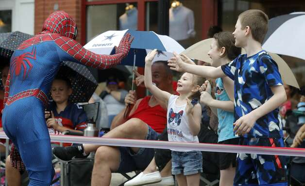Kalessi Harig, center, gets a high-five from a man in a Spiderman costume beside her siblings Aubree and Samuel during a Fourth of July parade at Market Street, Saturday, July 3, 2021, in The Woodlands. Photo: Jason Fochtman/Staff Photographer / 2021 ? Houston Chronicle