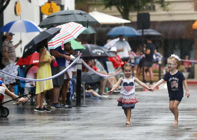 Ava Randazzo, left, and Faith Downing play in the rain before a Fourth of July parade at Market Street, Saturday, July 3, 2021, in The Woodlands. Photo: Jason Fochtman/Staff Photographer / 2021 ? Houston Chronicle