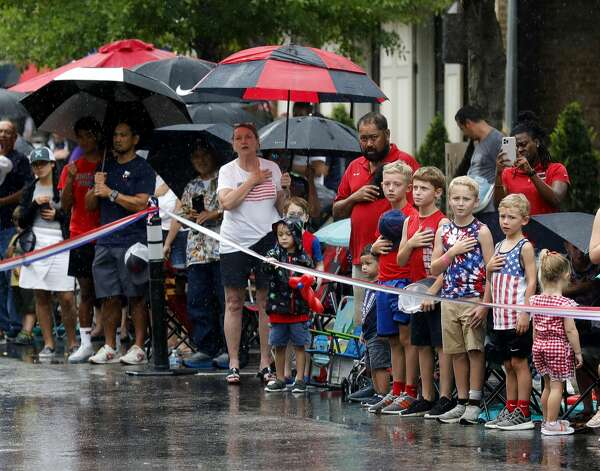 Parade goers stand for the national anthem during a Fourth of July parade at Market Street, Saturday, July 3, 2021, in The Woodlands. Photo: Jason Fochtman/Staff Photographer / 2021 © Houston Chronicle