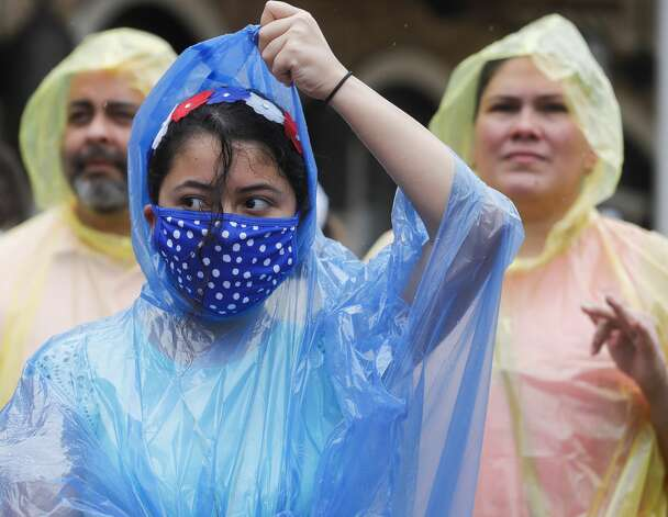 Louise Catenana puts on rain gear as she watches a Fourth of July parade at Market Street, Saturday, July 3, 2021, in The Woodlands. Photo: Jason Fochtman/Staff Photographer / 2021 © Houston Chronicle