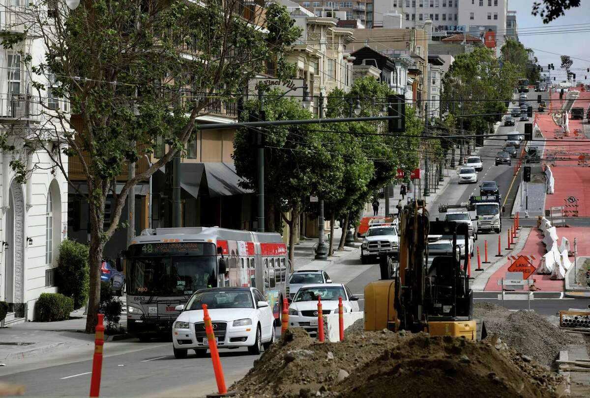 A Muni bus travels with other vehicles as construction continues on Van Ness Avenue near Filbert Street. The Van Ness Improvement Project is behind schedule, but the Municipal Transportation Agency says it will vastly improve public transportation and traffic through the busy corridor.