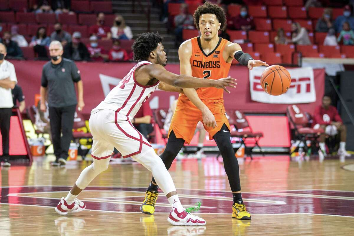 NORMAN, OK - FEBRUARY 27: Oklahoma State Cowboys guard Cade Cunningham (2) passes around Oklahoma Sooners guard Elijah Harkless (24) during the second half on February 27th, 2021 at Lloyd Noble Center in Norman Oklahoma. (Photo by William Purnell/Icon Sportswire via Getty Images)