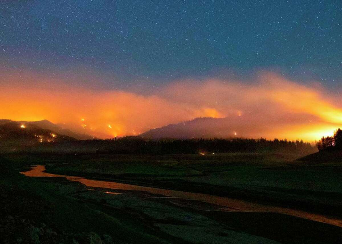 Flames surround drought-stricken Shasta Lake on Friday in a long-exposure image. The Salt Fire grew 2,400 acres overnight.