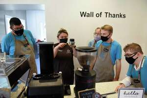 From left, employee Brian Paez, shift lead Maggie Lam, Abilis jo coach Suzanne Ford, employee Spencer Connolley, and employee David Mott make an espresso drink at Coffee for Good in Greenwich, Conn. Wednesday, June 30, 2021. Located on the campus of Second Congregational Church, Coffee for Good employs 24 people with disabilities, training them for permanent employment at other nearby businesses in the community.