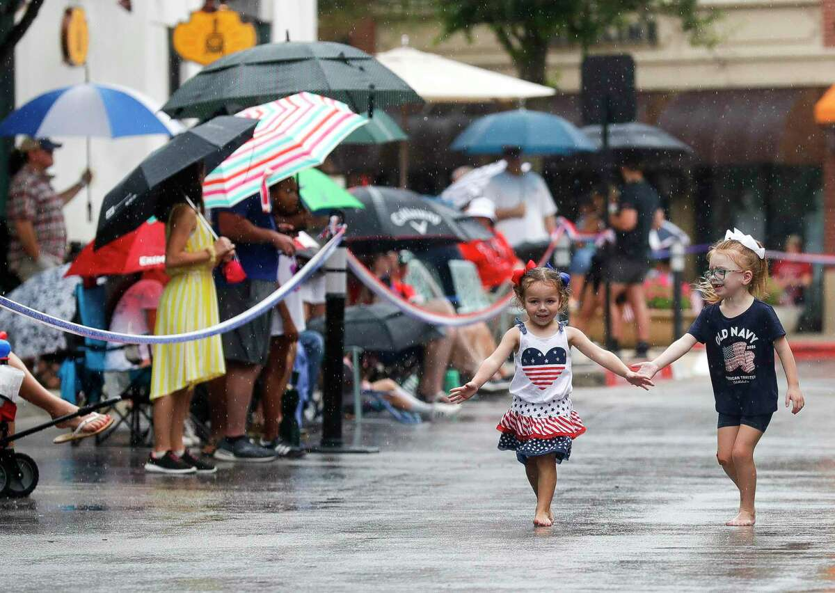 Ava Randazzo, left, and Faith Downing play in the rain before a Fourth of July parade at Market Street, Saturday, July 3, 2021, in The Woodlands.
