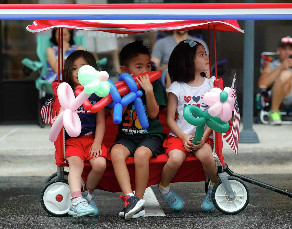 Mika Lee play with his balloon gun beside his siblings Stephanie and Emily as they wait for a Fourth of July parade at Market Street, Saturday, July 3, 2021, in The Woodlands.