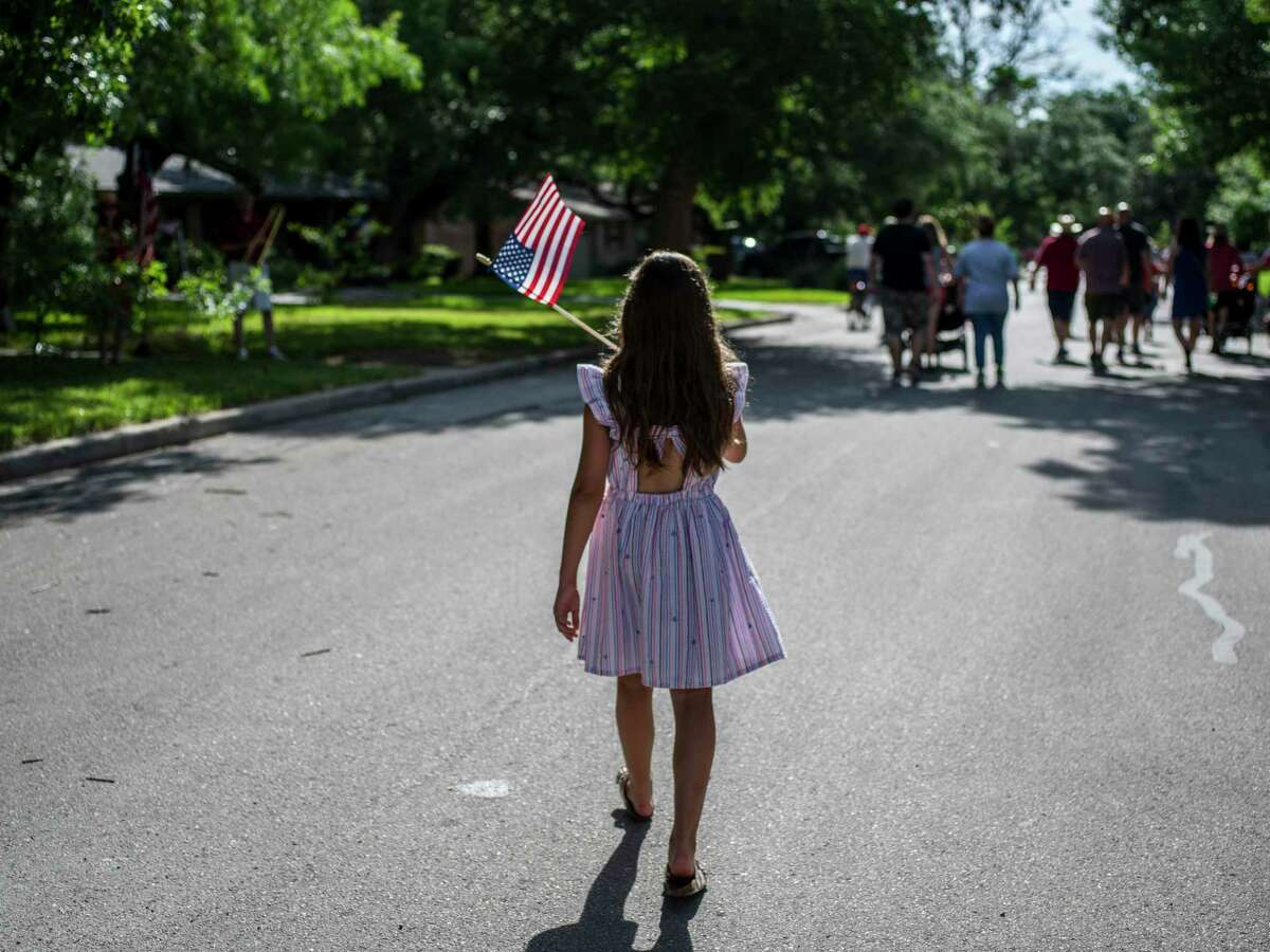 Community members wave flags and encourage neighbors to celebrate during the 25th annual Oak Park-Northwood Fourth of July Neighborhood Parade on Saturday. The neighborhood association organized the event.