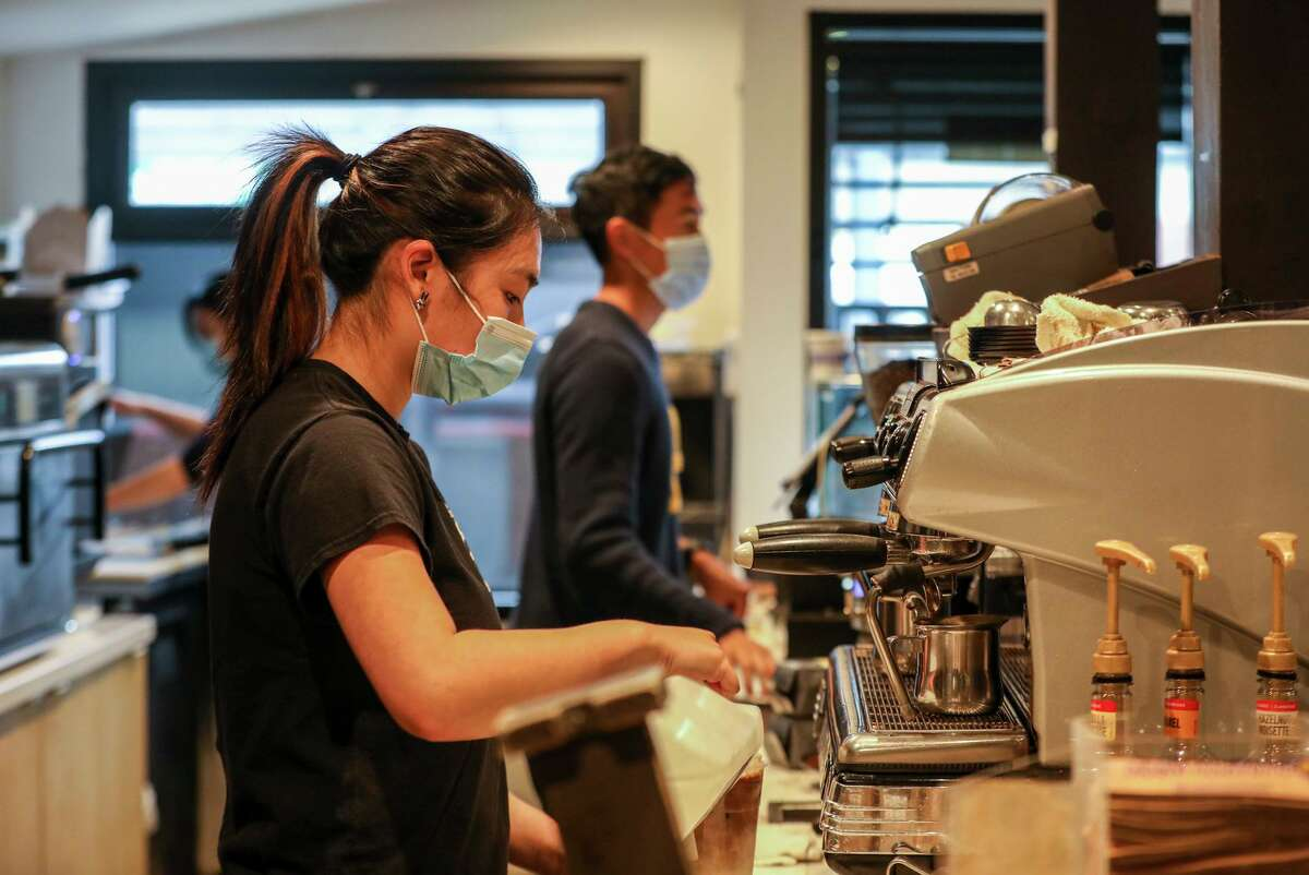 Jada Yee prepares a beverage at Henry's House of Coffee in San Francisco. While the coffee house doesn't require customers to wear masks, employees continue to do so due to confusing rollout of workplace safety measures statewide.