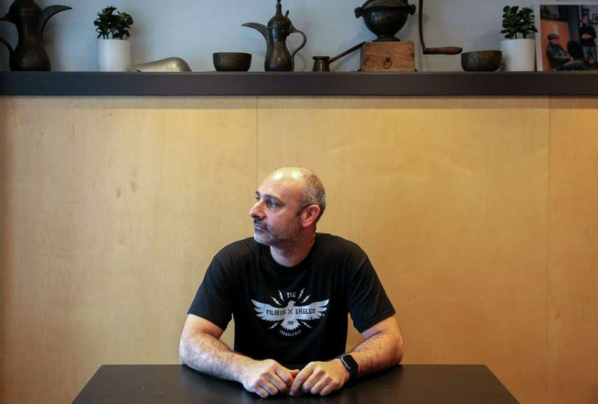 Owner Hrag Kalebjian sits inside Henry's House of Coffee in San Francisco. Kalebjian has his staff wear masks while at work because of the confusion caused by Cal/OSHA's issuing of workplace safety rules.