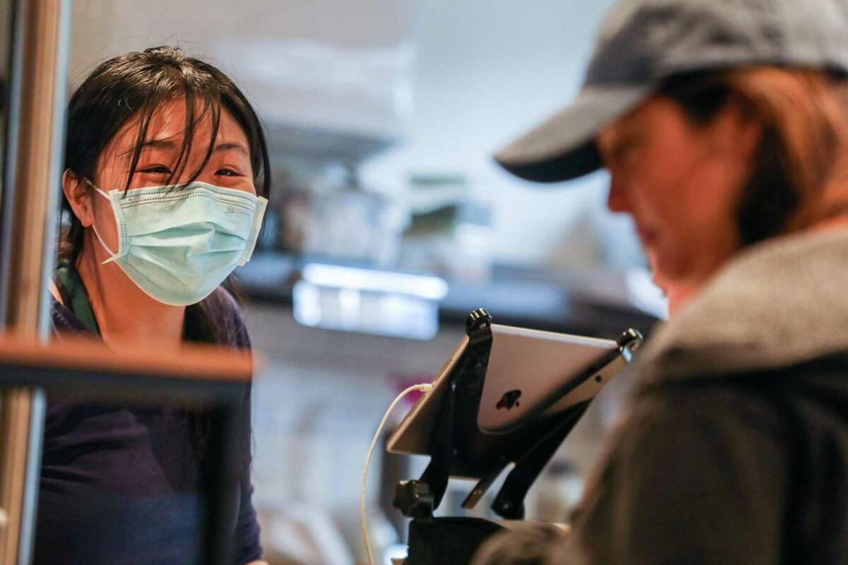 Ring Chen takes an order from customers at Henry's House of Coffee in San Francisco. The coffee shop is still requiring employees to wear masks due to a confusing rollout on workplace safety rules statewide.