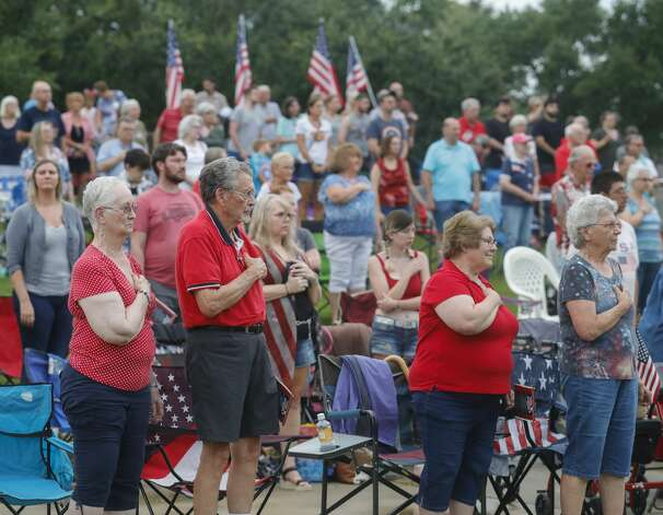Visitors stand as the Conroe Symphony plays the national anthem during a concert at Heritage Place Park, Saturday, July 3, 2021, in Conroe. Under the direction of its newly minted Music Director Anna-Maria Gkouni, the group performed a repertoire of patriotic pops from American composers. Photo: Jason Fochtman/Staff Photographer / 2021 © Houston Chronicle