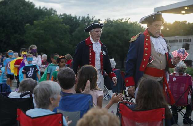 David Underdown and David Hamaker with Sons of the American Revolution leads a group of children dressed as superheros as the Conroe Symphony plays during a concert at Heritage Place Park, Saturday, July 3, 2021, in Conroe. Under the direction of its newly minted Music Director Anna-Maria Gkouni, the group performed a repertoire of patriotic pops from American composers. Photo: Jason Fochtman/Staff Photographer / 2021 © Houston Chronicle