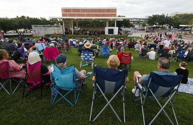 Visitors listen to the Conroe Symphony perform a repertoire of patriotic pops from American composers during a concert at Heritage Place Park, Saturday, July 3, 2021, in Conroe. Photo: Jason Fochtman/Staff Photographer / 2021 © Houston Chronicle