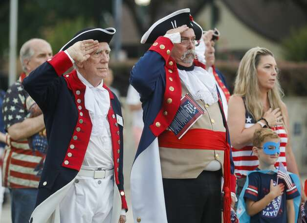 David Underdown and David Hamaker with Sons of the American Revolution salute as the national anthem is played as the Conroe Symphony plays the national anthem during a concert at Heritage Place Park, Saturday, July 3, 2021, in Conroe. Under the direction of its newly minted Music Director Anna-Maria Gkouni, the group performed a repertoire of patriotic pops from American composers. Photo: Jason Fochtman/Staff Photographer / 2021 © Houston Chronicle