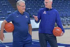 UConn basketball coaches Geno Auriemma (left) and Dan Hurley chat before filming a public service announcement in Gampel Pavilion Wednesday, June 9, 2021.