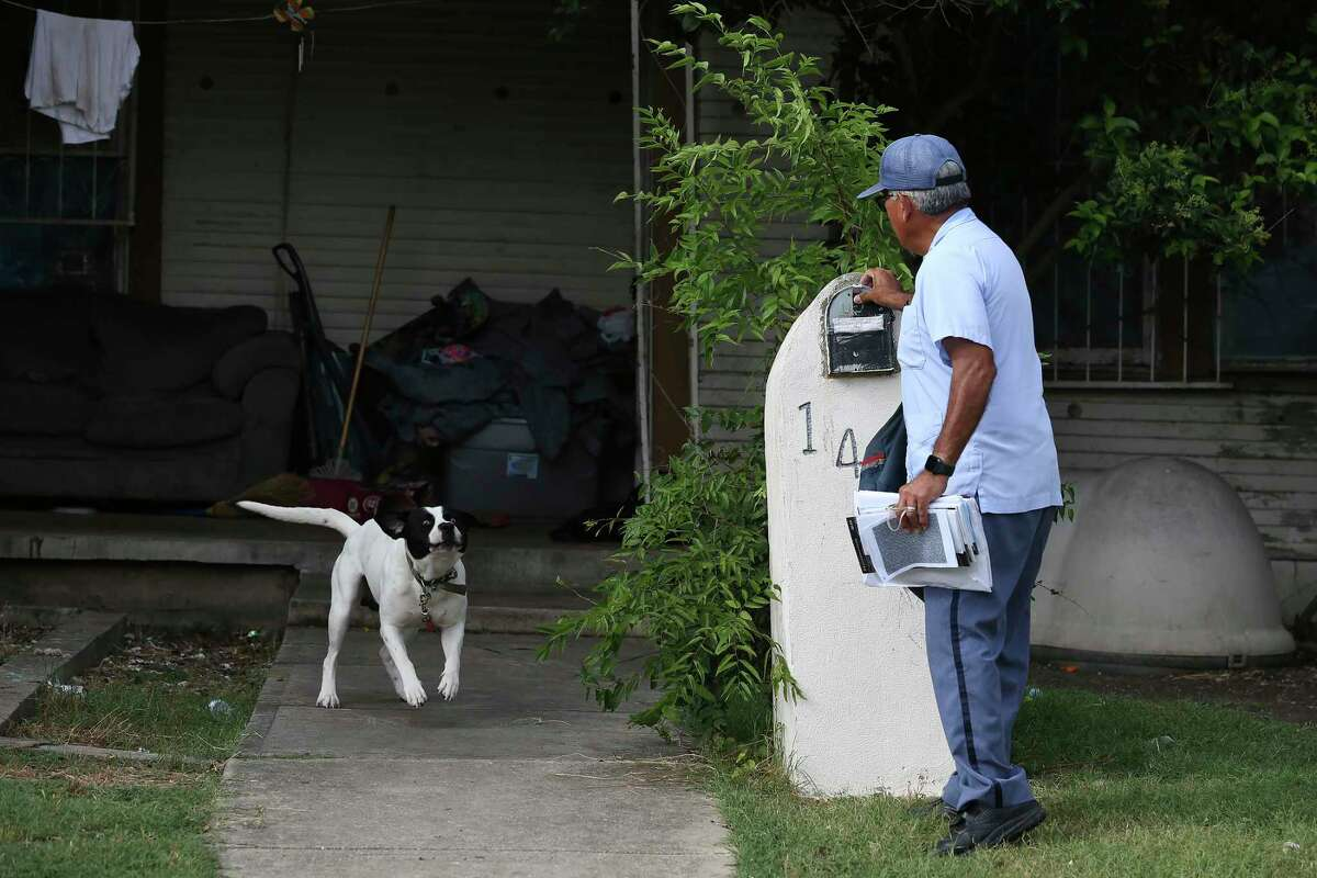 """A tied-up dog greets U.S Postal Service letter carrier Joe Valadez, 59, while he makes his rounds on the East Side. """"You never know what the dog is going to do,"""" Valadez says."""