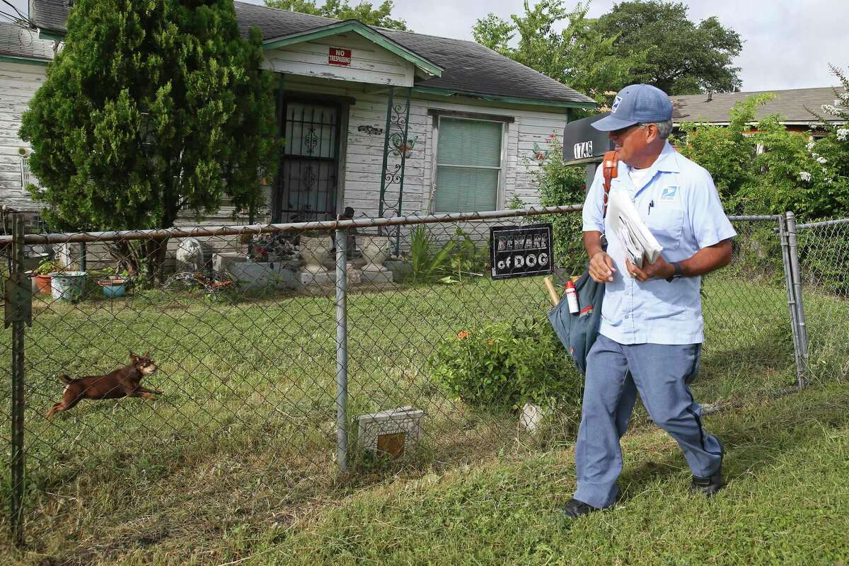 Postal worker Joe Valadez takes care of his route, walking along North Center Street on the East Side.