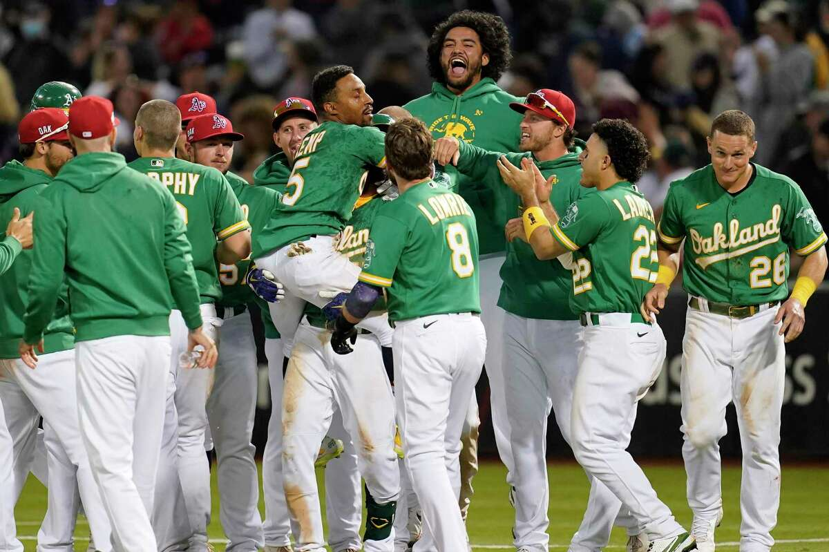 Oakland Athletics' Tony Kemp, middle left, is lifted by teammates after hitting a sacrifice fly that scored Seth Brown for the winning run during the twelfth inning of a baseball game against the Boston Red Sox in Oakland, Calif., Saturday, July 3, 2021. (AP Photo/Jeff Chiu)