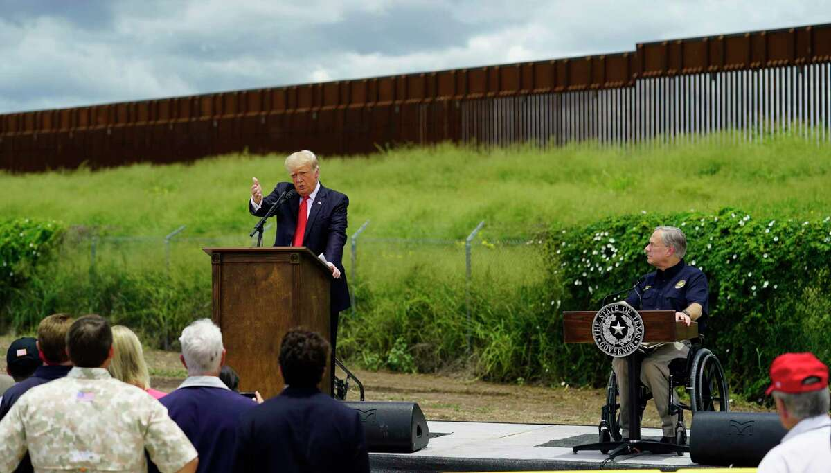 """Gov. Greg Abbott, right, listens to former President Donald Trump during a Wednesday visit to an unfinished section of border wall in Pharr. Some landowners who sued the Trump administration say they aren't """"just going to roll over and give up"""" now that Abbott has taken on a border wall project. Others say a wall is needed to protect people and property on the border."""