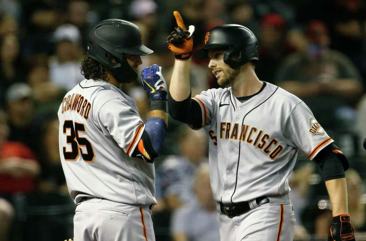 PHOENIX, ARIZONA - JULY 03: Austin Slater #13 of the San Francisco Giants is congratulated as he crosses the plate by Brandon Crawford #35 of the Giants after hitting a two-run home run against the Arizona Diamondbacks during the eighth inning of the MLB game at Chase Field on July 03, 2021 in Phoenix, Arizona. (Photo by Ralph Freso/Getty Images)