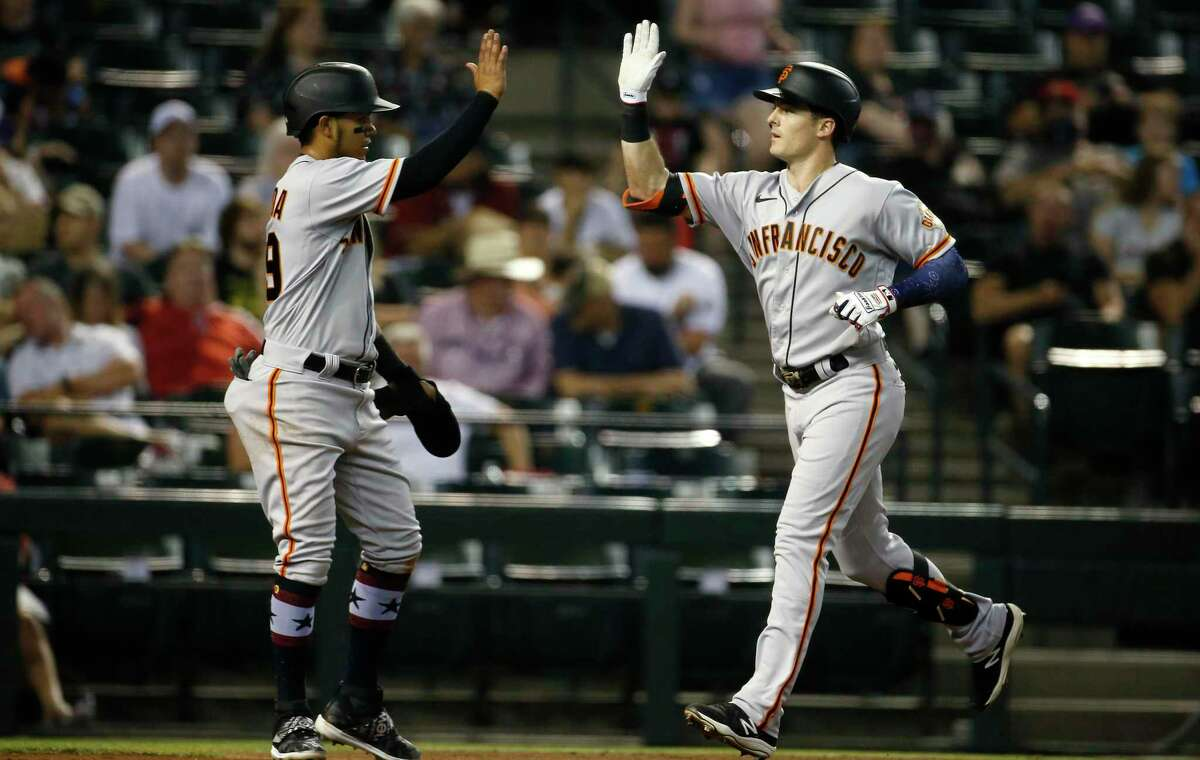 PHOENIX, ARIZONA - JULY 03: Mike Yastrzemski #5 of the San Francisco Giants (R) is congratulated as he crosses the plate by Thairo Estrada #39 of the Giants after hitting a two-run home run against the Arizona Diamondbacks during the third inning of the MLB game at Chase Field on July 03, 2021 in Phoenix, Arizona. (Photo by Ralph Freso/Getty Images)