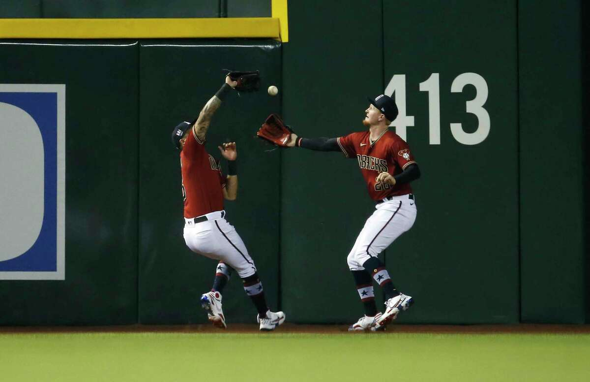 PHOENIX, ARIZONA - JULY 03: Outfielders David Peralta #6 and Pavin Smith #26 of the Arizona Diamondbacks can't make the catch of a deep fly ball hit by Brandon Crawford #35 of the San Francisco Giants during the third inning of the MLB game at Chase Field on July 03, 2021 in Phoenix, Arizona. (Photo by Ralph Freso/Getty Images)