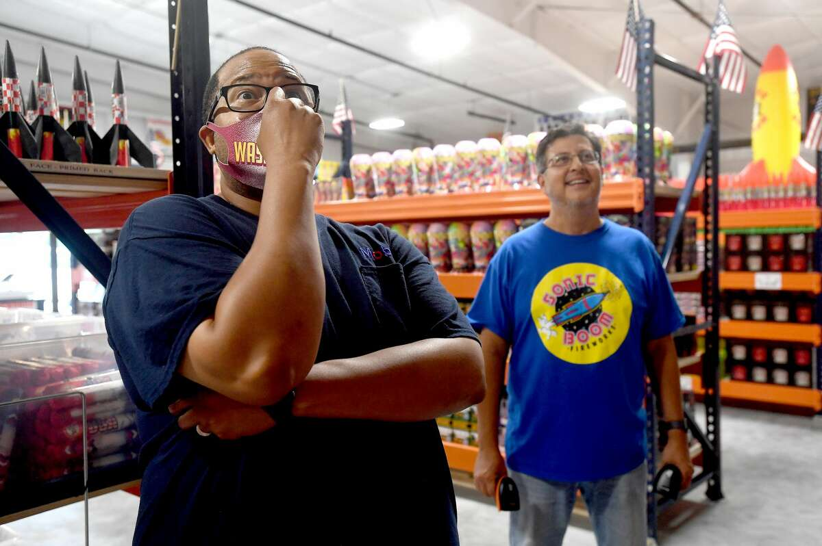 """Reginald Wilridge reacts as Sonic Boom's Jay Ramirez shows him a preview of the large Snow Cone's display while shopping for his family's Fourth of July celebration fireworks, which is also his wife's birthday. Wilridge stocked up for his annual fireworks celebration, joking, """"any chance I get to set a fire to something is a good day."""" The store, located on U.S. 90 west of Beaumont will be open at least until midnight Saturday and until midnight Sunday. Ramirez says, as in years past, they will grab some fireworks after store closing to have a mini-show after closing. Photo made Friday, July 2, 2021 Kim Brent/The Enterprise"""