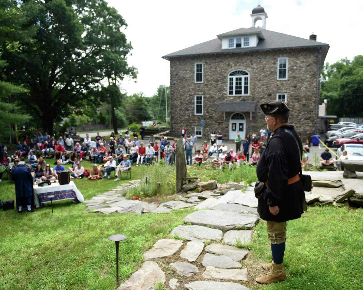 Al Cawthra, dressed as a Revolutionary militia member, attends the third annual Independance Day reading at the Stamford History Center in Stamford, Conn. Sunday, July 4, 2021. Folks dressed in character as Isaac Quintard and Elizabeth Cady Stanton read the Declaration of Independence and Declaration of Rights and Sentiments on the steps of the Hoyt-Barnum House, Stamford's oldest dwelling.