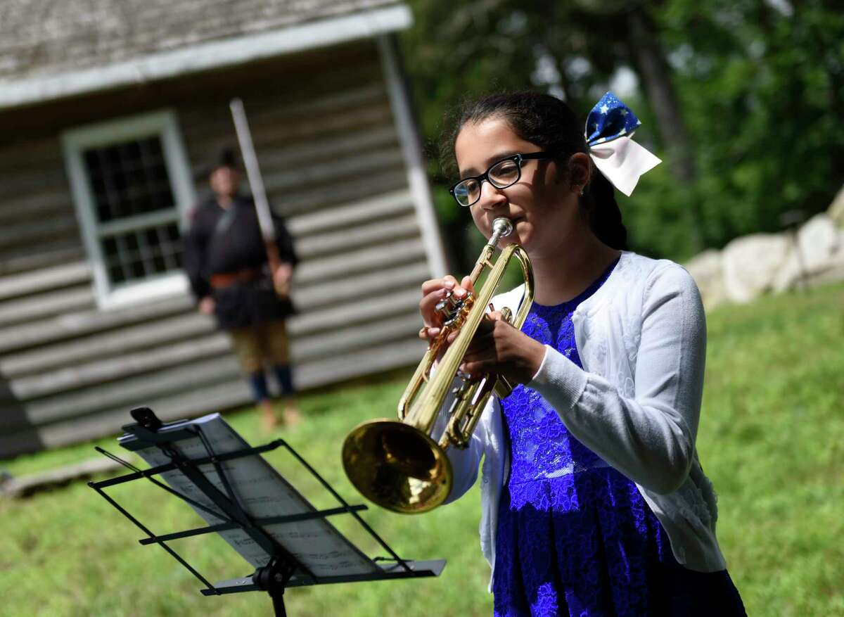 """Project Music student Emily Barreto performs """"Yankee Doodle"""" during the third annual Independance Day reading at the Stamford History Center in Stamford, Conn. Sunday, July 4, 2021. Folks dressed in character as Isaac Quintard and Elizabeth Cady Stanton read the Declaration of Independence and Declaration of Rights and Sentiments on the steps of the Hoyt-Barnum House, Stamford's oldest dwelling."""